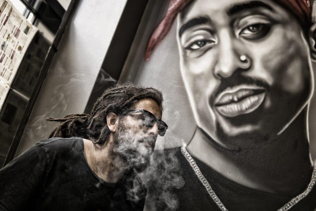 Røykende mann foran grafittivegg